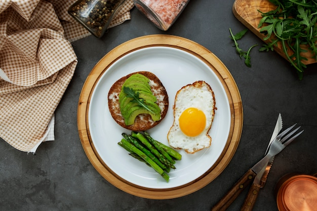 アボカドトーストサンドイッチと目玉焼きとアスパラガスの白いプレート。健康食品または朝食。