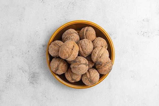 明るい質感の表面に丸皿のクルミ。健康的なナッツ、健康食品。