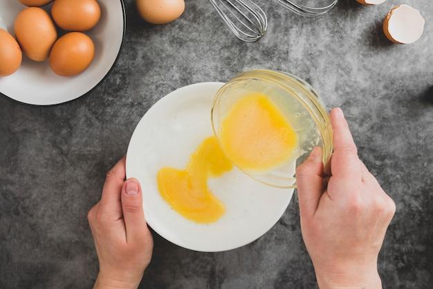 オムレツを調理します。女性の手がオムレツを調理し、新鮮な卵を割る。食品フラットが横たわっていた。