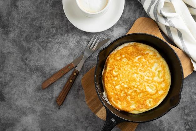 黒フライパンのオムレツ、暗い食べ物の写真。新鮮な朝食の平面図です。