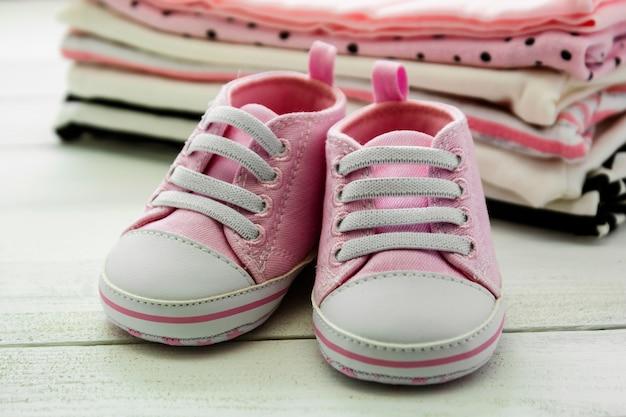 Розовая детская обувь и новорожденная одежда. концепция материнства, образования или беременности с космосом экземпляра.