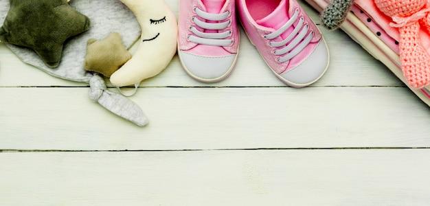 Розовая детская обувь, одежда для новорожденных и мягкие игрушки. концепция материнства, образования или беременности с космосом экземпляра. банер.