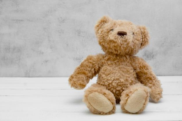 Игрушка плюшевого медвежонка мягкая на серой изолированной предпосылке ,. концепция образования, воспитания детей и ребенка. копировать пространство