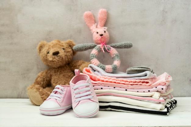 Розовая детская обувь, одежда для новорожденных и мягкие игрушки. концепция материнства, образования или беременности с космосом экземпляра.