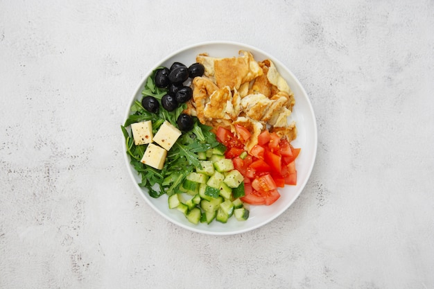 健康的な朝食。新鮮な野菜のサラダロケット、トマト、キュウリ、オリーブ、チーズのオムレツ。上面図。