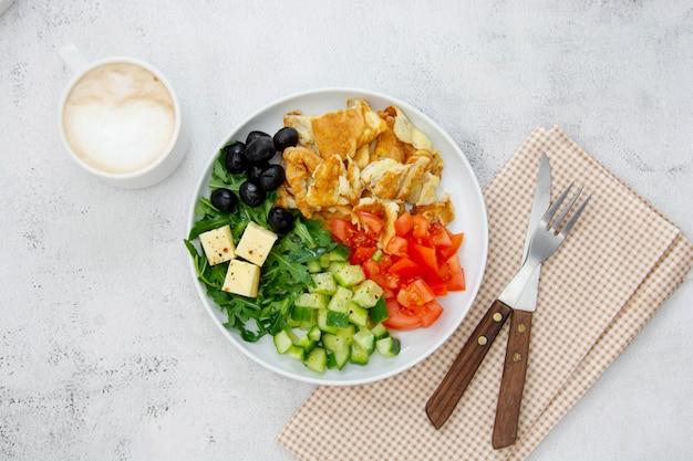 Свежий омлет на завтрак со смешанными овощами: руккола, помидоры, огурцы, оливки, сыр. вид сверху.