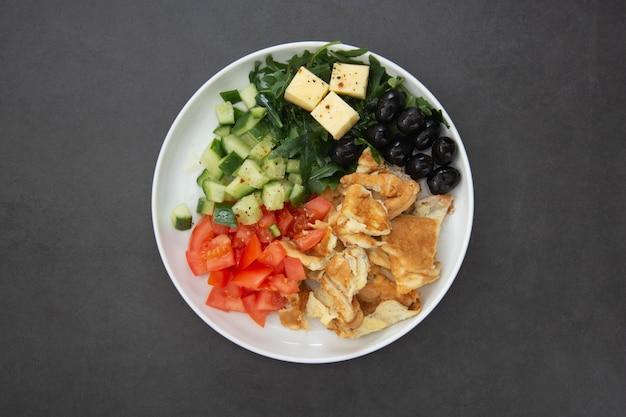 健康的な朝食。新鮮な野菜のサラダロケット、トマト、キュウリ、オリーブ、チーズのオムレツ。コピースペースと暗いテーブル。上面図。