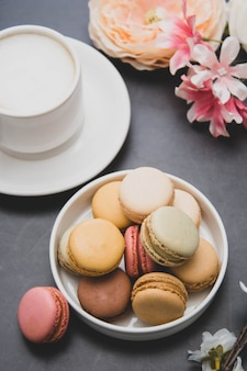 Чашка кофе и миндальное печенье на красочные черный стол. вид сверху.