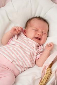泣いている新生児の女の子。腹痛。赤ちゃんの肖像画。