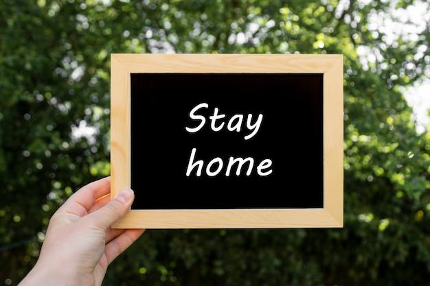 Оставайся дома словами. пустой, пустой доске с копией пространства. социальная дистанция, будьте в безопасности.
