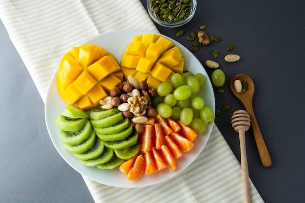おいしいフルーツの盛り合わせが分離されました。マンゴー、キウイ、柑橘類、ナッツ、ブドウ。