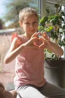 ウィンドウ上の彼女の指でハートのジェスチャーを作る小さな女の子。