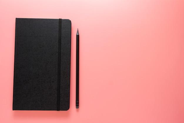 在宅勤務。ピンクのテーブル、フラットレイアウト、コピースペースの上に黒い鉛筆で黒いノートブックまたはジャーナル。