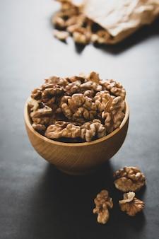 Грецкие орехи в деревянной миске на темном столе