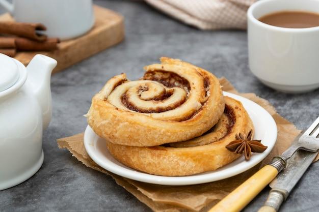 Булочка с булочкой с корицей крупным планом. коричневое вихревое тесто на завтрак на сером