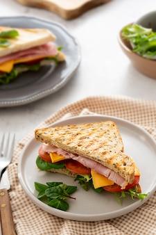 Свежий жареный бутерброд с ветчиной, овощами и сыром на завтрак.