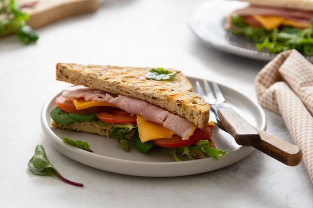 ハム、野菜、チーズのサンドイッチ、トーストしたパン。朝食、昼食。