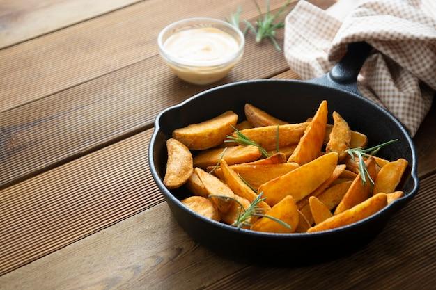 Зажаренная в духовке картошка в сковороде сковороды на деревянном столе. домашние жареные ломтики золотого картофеля.