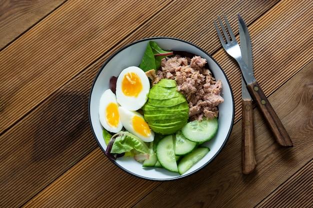 Здоровый салат из тунца и яиц с авокадо и свежими листьями зеленого салата.