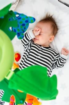 Вид сверху малыш лежал в кроватке кровати, глядя на кроватку мобильных игрушек.