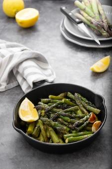 新鮮なグリーンローストアスパラガスの黒い鉄鍋。