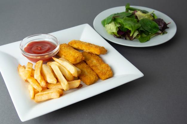 Рыба и чипсы с картофелем фри - нездоровая пища, серый фон.