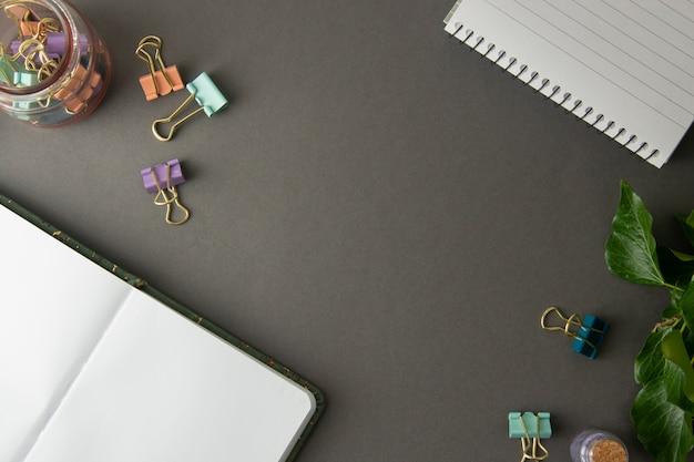 ノートブックを開く、作業テーブル、灰色の背景。クリエイティブワークスペース、事務用品。