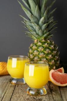 ジュースグラスとフルーツ - パイナップル、オレンジ。夏の冷たい飲み物。