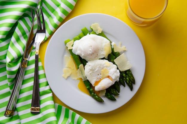 朝食 - 半熟卵とパルメザンチーズのアスパラガスのサラダ。灰色の背景
