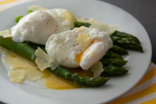 半熟卵とパルメザンチーズのアスパラガスのサラダ。灰色の背景