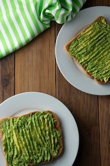 健康的なアボカドサンドイッチ、トースト。木製の背景に、マッシュアボカドペースト。