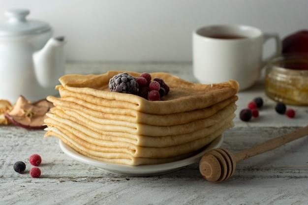 薄いパンケーキのスタックは、イチゴとブルーベリーで飾られました。健康的な朝食。