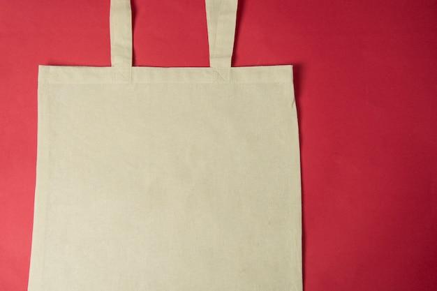 キャンバスエコバッグ、カラフルな赤い背景の上の買い物袋をトートします。無駄のないコンセプト