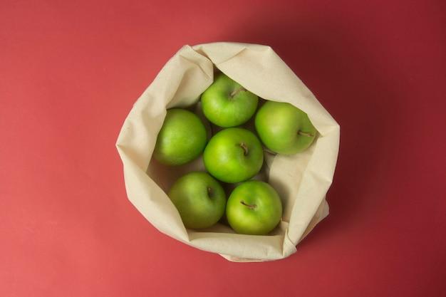 Зеленые яблоки в сумка на красном фоне. ноль отходов концепции.