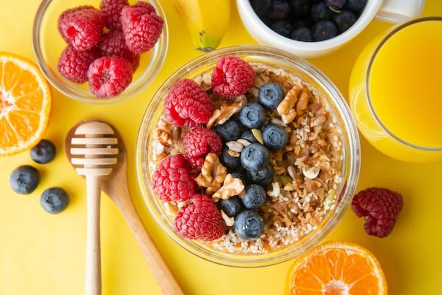 Зерновые с фруктами, ягодами на завтрак. здоровый завтрак, желтый фон.