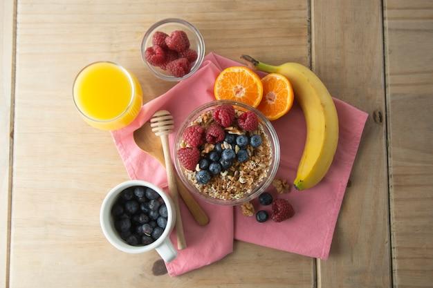 Зерновые с фруктами, ягодами на завтрак. здоровый завтрак, деревянный фон.
