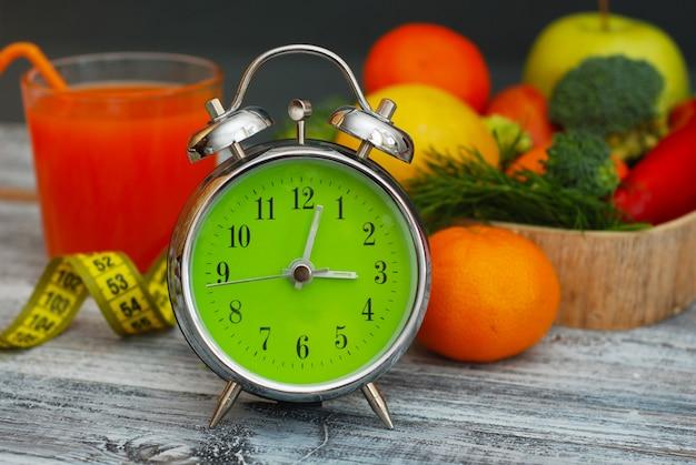 体重を減らすための時間。果物、野菜、目覚まし時計。ダイエット