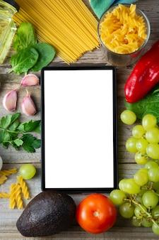 健康食品のコンセプトです。新鮮な野菜とタブレットの画面。スペースをコピーします。