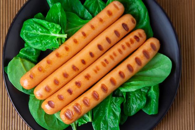 Жареные колбаски, изолированные на белом фоне с листьями шпината, на деревянном столе