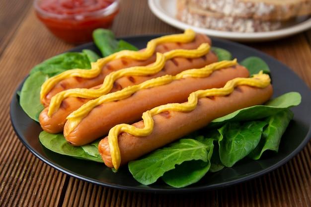 Колбаски гриль с горчицей на белой тарелке с листьями шпината, на деревянном столе