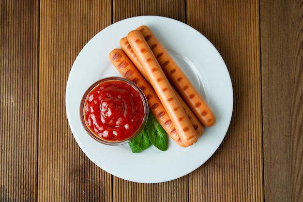 Колбаски гриль с соусом кетчуп на деревянном столе