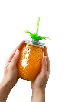 夏の飲み物、ジュースまたはカクテル。オレンジジュースでいっぱいパイナップルメイソンジャーを持つ女性の手