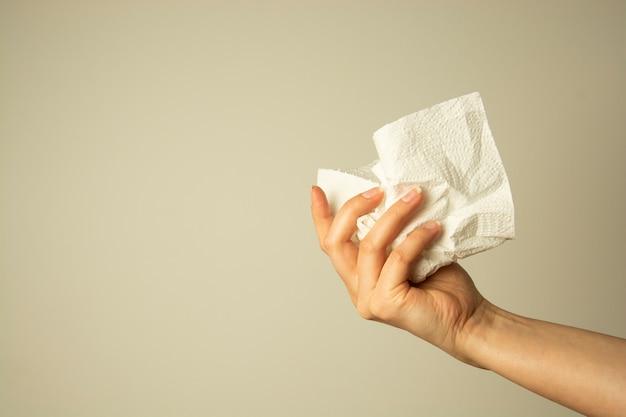 Женская рука держит белую бумажную салфетку или платок. здравоохранение, простуда, аллергия концепция.