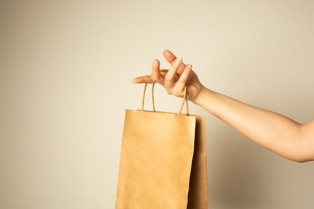 Крупный план женской руки держа пакет бумаги ремесла, насмешка дизайна вверх. концепция нулевой пасхи.