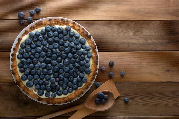 ブルーベリーのタルト、またはクリームとベリーのケーキ。自家製食品、木製、素朴な背景。