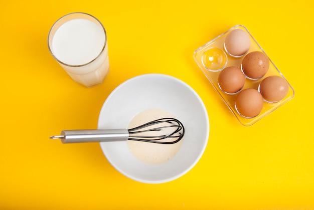 Ингредиенты для выпечки. готовим блины. желтый фон завтрак.