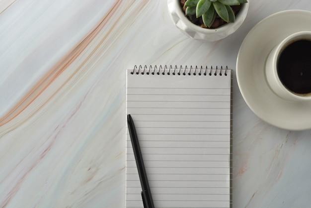 一杯のコーヒー、大理石の机の上の多肉植物でノートブックを開く。職場、作業テーブル上面図。