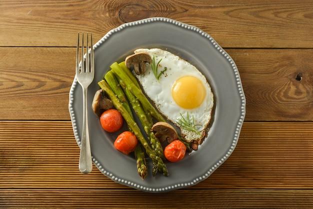 アスパラガス、目玉焼き、チェリートマトの朝食。木製のテーブル