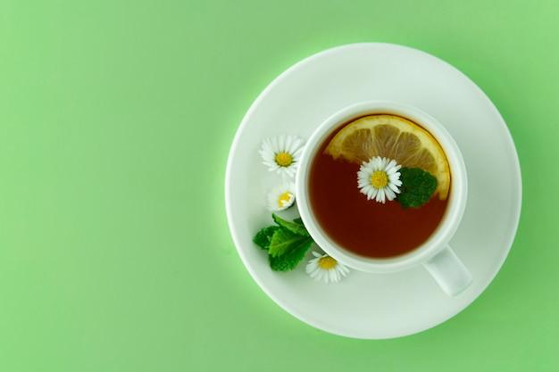 紅茶とカモミールのカップ。ハーブの天然茶のコンセプトです。カモミールの花と紅茶の白いカップ。