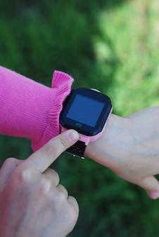 Умные часы на руке маленькой девочки. ребенок, использующий технологии.
